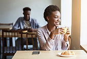Millennial African American girl relaxing with cup of coffee in cozy cafe, empty space