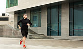 Sporty young man running in city center in the morning