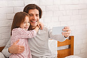 Positive father and daughter taking selfie in bedroom