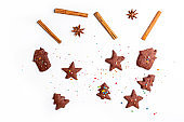 Christmas food background with cut out chocolate shortbread in  form of Christmas trees, stars and houses. Flat lay on white background. Holiday baking concept, homemade child cookies and gingerbread/