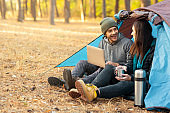 Romantic couple camping outdoors, sitting in tent with laptop