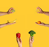 Healthy eating. Male hands showing organic vegetables and fruits on orange background, empty space. Collage