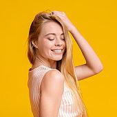 Teen Beauty. Cute Young Girl Enjoying Touching Her Beautiful Blond Hair