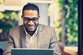Smiling afro guy in glasses listening to music at office