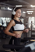 Pretty girl with headphones jogging on treadmill in gym