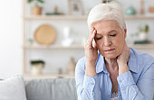 Senior Woman Suffering From Headache At Home, Feeling Unwell