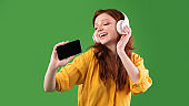 Happy Girl Singing Holding Phone Like Microphone Over Green Background