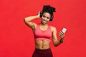 Joyful sporty woman listening to music while training