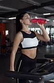Fit young girl drinking water on treadmill in gym