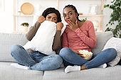 Frightened black girls watching horror together at home