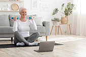 Active senior woman in sportswear exercising with dumbbells, practicing fitness at home, empty space