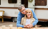 Smiling mature man hugging his beautiful wife in front of camping vehicle outdoors