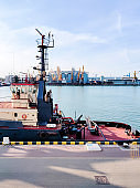 Tugboat assist on a pier in the harbor, cargo sea port over the sea, Floating cargo crane, Granary elevators, harbor, boats and cranes. Industrial scenery of the sea cargo port.