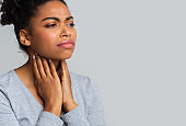 Afro woman suffering from sore throat, touching her neck