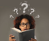 Puzzled black girl with book having trouble understanding school program, collage with question marks