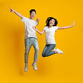 Carefree asian millennial man and woman jumping in air
