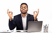 Black man meditating in office coping with stress