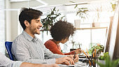 Young guy enjoying his job, working with colleagues in office