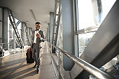 Smiling Black Entrepreneur Using Phone App Walking In Airport Indoors