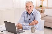 Senior man using laptop at office and looking at camera