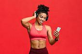 Happy black fitness girl choosing music on smartphone for exercising