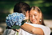 Happy Just-Married Couple Embracing Standing Outdoors, Focus On Wedding Bouquet