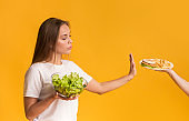 Confident young woman refusing plate with junk food and choosing salad