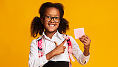 School Girl Pointing Finger At Empty Paper Card, Studio Shot