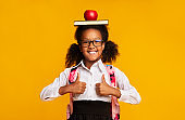 Schoolgirl Holding Book And Apple On Head Gesturing Thumbs-Up, Studio