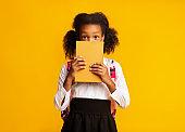 Shy African American Schoolgirl Hiding Behind Book, Studio Shot