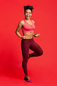 Happy fitness girl exercising over red background