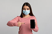 Young Woman In Medical Mask Pointing At Smartphone With Black Screen