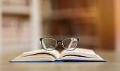 Opened book with glasses, bookshelves in background