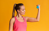 Sporty young girl demonstrating biceps, excercising with dumbbells on yellow background