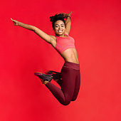 Carefree athletic girl in sportswear happily jumping up