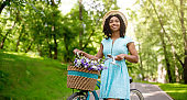 Millennial African American woman with bicycle at park on summer day, blank space