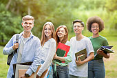 University Friends. Outdoor Portrait Of Diverse Multiracial Students With Workbooks Posing Together