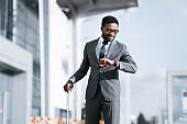 Businessman Smiling Looking At Wristwatch Arriving At Airport In Time