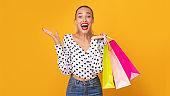 Overjoyed woman showing shopping bags at studio