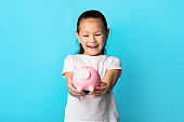 Little girl with piggy bank, studio shot, copy space