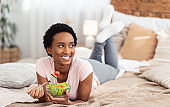Healthy vegan diet. Smiling black lady lying on bed at home with bowl of fresh vegetable salad, copy space. Panorama