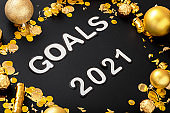 Goals 2021 text lettering on black background in frame made of gold Christmas festive decor. New year 2021 goals, resolution check list wishlist. Close up