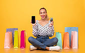 Happy woman with shopping bags, phone and plastic card