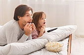 Single father watching horror with little daughter
