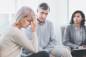 Sad husband and wife listening to psychotherapist
