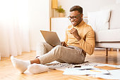 Cheerful Man Working On Laptop Sitting At Home, Selective Focus
