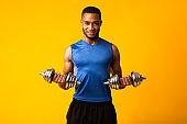 Afro bodybuilder raising hands pumping up dumbbells