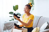 Happy black woman unpacking parcel with clothing and shoes