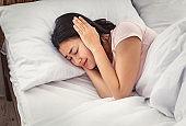 Asian Woman Having Ear Pain Covering Ears Lying In Bed
