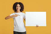 Advertising space and customer advice. Smiling woman holding banner with blank space